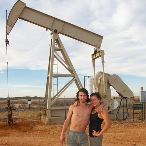 Andrew Ucles and Laura Zerra infront an oil well